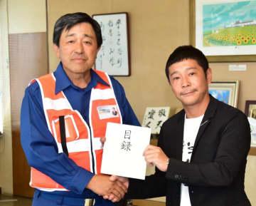 9月に行われた被災地訪問で、金丸市長(左)に目録を手渡す前澤さん(9月30日、同市提供)