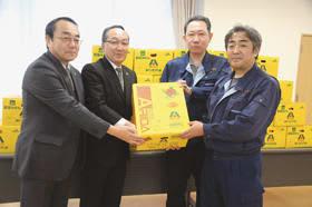みかん35箱を届けた丸果室蘭青果の石田次長(写真右)と山田次長(写真右から2人目)