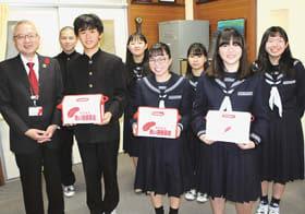 募金箱を手に記念写真に納まる港北中生徒会メンバーと米野事務局長(左)