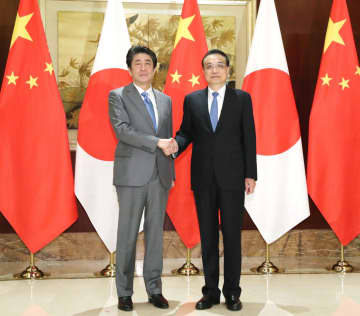 会談前、握手する安倍首相(左)と中国の李克強首相=25日、中国・成都(代表撮影・共同)