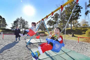 雪のない青空の下、元気にブランコをこぐ子どもたち=12月25日、福井県福井市の福井少年運動公園