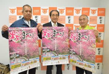 もとぶ八重岳桜まつりへの来場を呼び掛ける當山清博会長(右)ら関係者=本部町役場