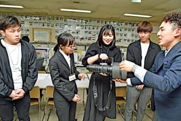 スポーツ取材に使う望遠レンズの重さに驚く学生たち=25日、鳥取市富安2丁目の新日本海新聞社