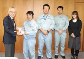 米野事務局長(左)に目録を手渡す土門執行委員長ら