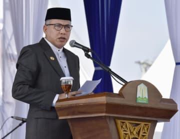 26日、インドネシア・シグリで開かれた追悼式典で、あいさつするノファ・イリヤンシャ州知事代行(共同)