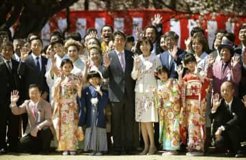 「桜を見る会」で招待者と記念写真に納まる安倍首相(中央)ら=4月、東京・新宿御苑