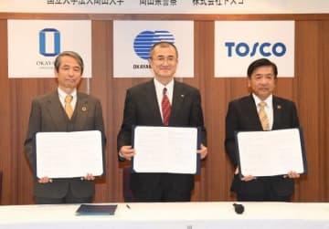 署名した協定書を披露する(左から)槇野学長、桐原本部長、橋本社長