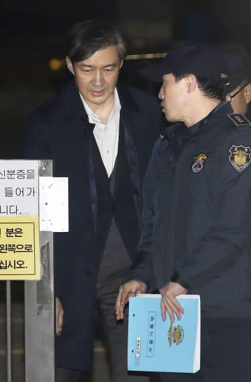 27日、逮捕状請求の棄却を受け、ソウル東部拘置所を出る韓国のチョ・グク前法相(左)(聯合=共同)