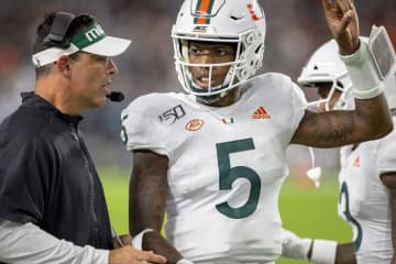 Miami quarterback N'Kosi Perry (5) speaks to offensive coordinator Dan Enos on the sideline in the second quarter against Virginia at Hard Rock Stadium in Miami Gardens, Fla., on Friday, Oct. 11, 2019. - Daniel A. Varela/Miami Herald/TNS
