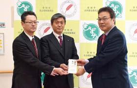 市社協にVOICEチャリティーライブの益金の一部を寄付する川田代表(中央)ら関係者