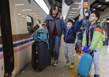 古里や観光地へ向かう人たちで混雑するJR東京駅で、新幹線に乗り込む家族連れ=27日午後