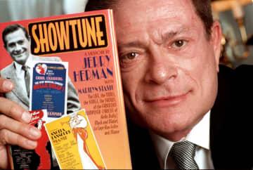 自著を持ってみせるジェリー・ハーマン氏(ニューヨーク、1996年撮影。AP=共同)