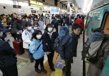 古里や観光地へ向かう人たちで混雑するJR東京駅で、新幹線に乗り込む人たち=28日午前