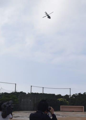 (資料写真)普天間第二小学校の上空周辺を飛行する米軍ヘリ=宜野湾市新城の同小