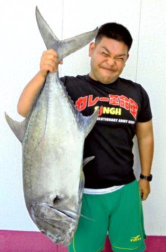 津堅島で107.5センチ、15.6キロのロウニンアジを釣った魚住海さん=17日