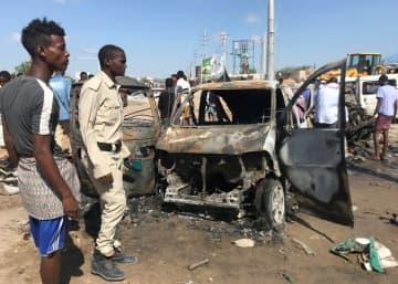 28日、ソマリアの首都モガディシオで爆発現場を調べる関係者ら(ロイター=共同)