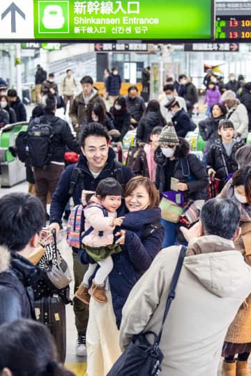 再会を喜ぶ帰省客らで混雑するJR八戸駅の改札口=28日午後1時半すぎ