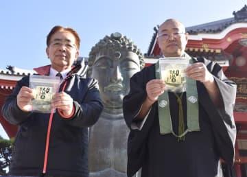 大仏の前に新設した写真スポットで新商品のサンプルを紹介する多部田社長(左)と平幡住職=銚子市