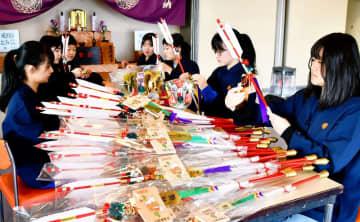 絵馬や鈴を取り付けてかぶら矢を準備する高校生=12月28日、福井県坂井市の成田山福井別院