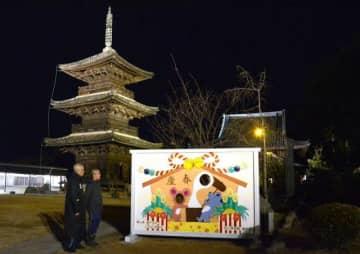 闇夜に浮かび上がる餘慶寺三重塔。20回目を記念した「顔出し絵馬」も設置されている