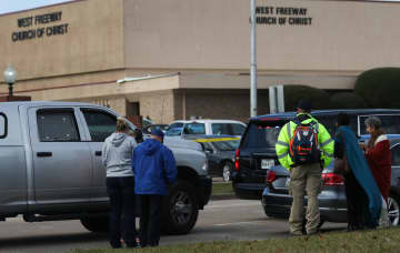 People stand near scene where two people where shot dead and another is in critical condition after a church shooting at West Freeway Church of Christ, on Dec. 29, 2019 in White Settlement, TX. - Juan Figueroa/Dallas Morning News/TNS