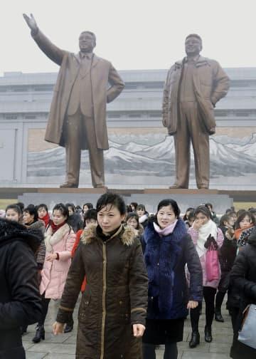 故金日成主席(左)と故金正日総書記の銅像が立つ万寿台の丘に訪れた市民ら=30日、平壌(共同)