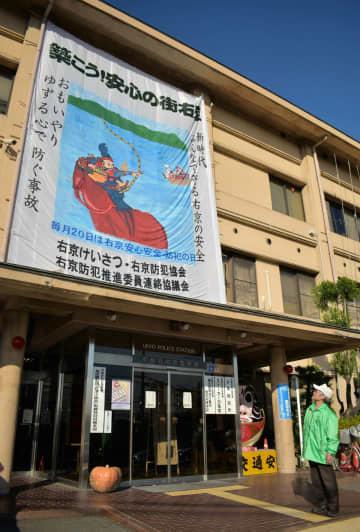 右京署の玄関に設置された大だこを見上げる椿原さん。地域の安全を願って長年手作りしてきた(京都市右京区)