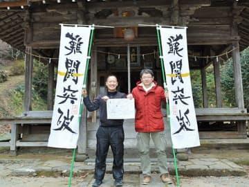 スタンプ用紙と目印ののぼりを持つ「TMOなんかん」の山崎彰悟委員長(左)=南関町