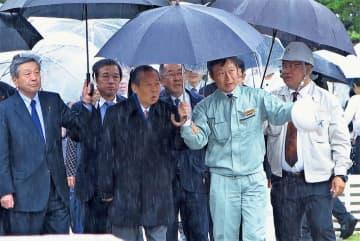 雨の中、首里城を視察する自民党の二階俊博幹事長(右から4人目)=30日、首里城