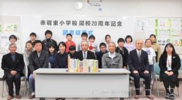 図書を寄贈した小保方会長(中央)と図書委員ら