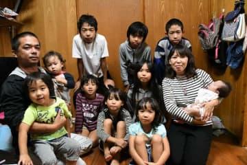 子どもたちに囲まれる新川大介さん(左端)と末っ子の心望ちゃんを抱く亜由美さん。長男と次男はこの日は外出中だった=うるま市みどり町