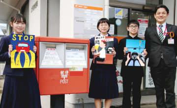 飲酒運転などの撲滅を呼び掛ける年賀状をデザインした生島さん(左)、原さん(左から2人目)、松尾さん(右から2人目)と松崎局長=長崎市磯道町、土井首郵便局
