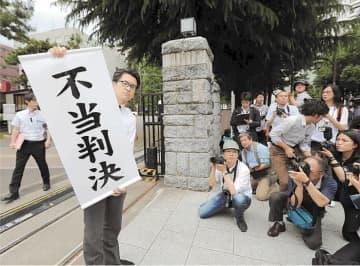 「不当判決」と書かれた垂れ幕を掲げる原告代理人=5月28日、仙台市