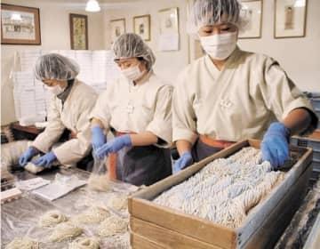 年越しそばの袋詰め作業に追われる従業員=盛岡市の東家本店