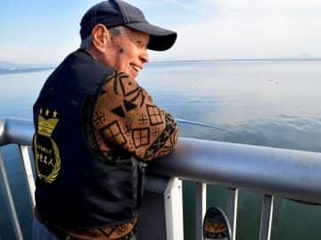「外来魚釣り上げ永世名人」と刺しゅうされたベストを着て、琵琶湖にさおを投げ入れる越田さん(大津市)