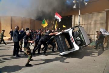米大使館敷地内の物を壊す人々=31日、イラク・バグダッド(AP=共同)