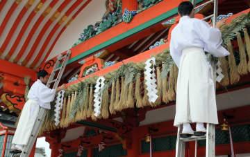 大しめ縄を張って迎春準備を整える神職(26日、京都市伏見区・伏見稲荷大社)