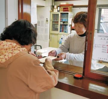 菅会館で義援金を受け取る地元被災者