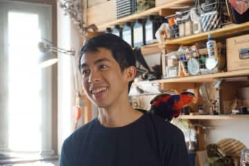 Cheung and his 18-year-old parrot. Photo: Varsity.