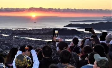 写真を拡大 令和初の初日の出に歓声を上げながら写真を撮る人々=徳島市の眉山山頂