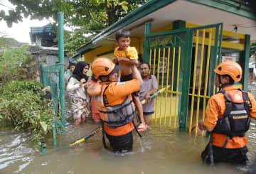 浸水した住宅からインドネシア捜索救助庁の隊員らに救助される子ども=2日、ジャカルタ近郊ブカシ(同庁提供・共同)