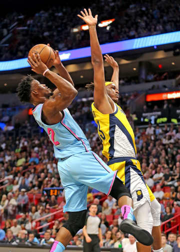 The Miami Heat's Jimmy Butler (22) takes aim at the basket as the Indiana Pacers' Myles Turner (33) defends in the first quarter at the AmericanAirlines Arena in Miami on Friday, Dec. 27, 2019. - CHARLES TRAINOR JR/Miami Herald/TNS