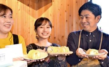 奥武蔵ロールケーキのお披露目会で、「結ずロール」をPRする浅見敦さん(右)と学生=越生町小杉のオクムサ・マルシェ