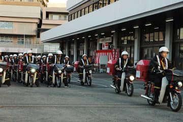 年賀状を積んだバイクに乗り、各家庭に向かう配達員たち=1日早朝、さいたま市南区のさいたま中央郵便局