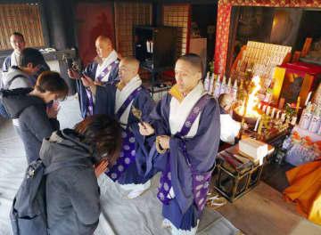 護摩木が燃え上がる堂内で錫杖の加持を受ける参詣者=3日、大阪市天王寺区の四天王寺