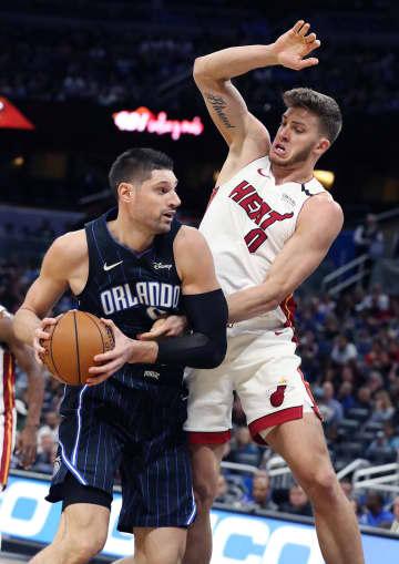 The Miami Heat's Meyers Leonard (0) fouls the Orlando Magic's Nikola Vucevic at the Amway Center in Orlando, Fla., on Friday, Jan. 3, 2020. - Stephen M. Dowell/Orlando Sentinel/TNS