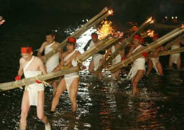 たいまつを手に駅館川を渡る締め込み姿の男衆ら=4日夜、宇佐市の鷹栖観音