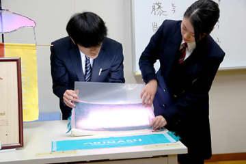 光を当てると文字が消える不思議な布を示す斎藤凱斗さん(左)と我妻花音さん=米沢市・米沢工業高