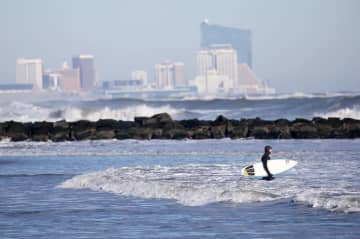 A surfer wades into the ocean in Ocean City, with the Atlantic City skyline behind him in 2016. (Lori M. Nichols/)