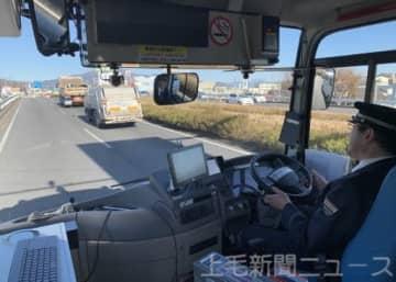 実証実験で国道17号を走る自動運転バス。運転手がハンドルから手を離しながらも走行し、バス停へも停車した=昨年12月、渋川市